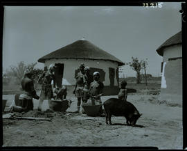Transkei, 1968. Group of people around pots in kraal.