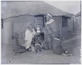 Pretoria district, 1952. Ndebele women and children in front of hut.