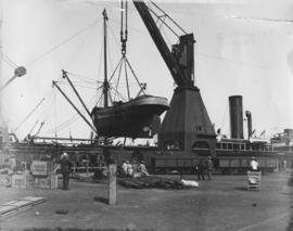 The 'Caledonia' being lifted by crane in dock yard.