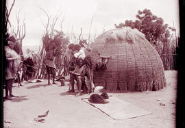 Swaziland, 1933. Swazi men preparing for the dance outside a hut.