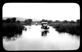 Round in Nine Tours - two motors cars crossing wide water body.
