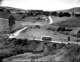 """1951. Two SAR buses on country road with bridge, with a settlement in the distance."""