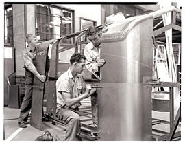 """Johannesburg, 1962. Apprentices fitting sheetmetal panel to coach body in Road Transport Se..."