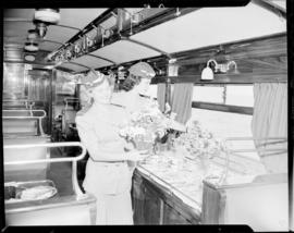 Cape Town. Travel hostesses arranging flowers in staff dining saloon No 219 'Protea'.