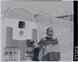 Pretoria district, 1952. Ndebele woman at decorated wall.