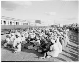 Bechuanaland, 17 April 1947. Crowd seated alongside Pilot Trains at wayside station.
