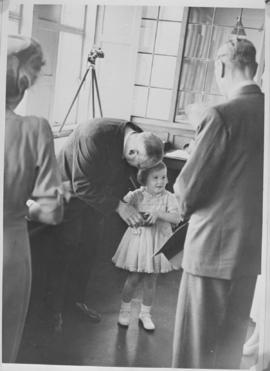 Kimberley, 18 March 1947. Little girl being coached in presenting a gift to Princess Elizabeth at...