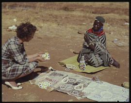 Woman inspecting beadwork from street vendor.