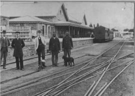 Grahamstown, 1895. Stationmaster and staff with station building in the distance.