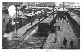 Cape Town, 1893. Station platforms with a mainline train ready to depart behind a CGR 6th Class o...