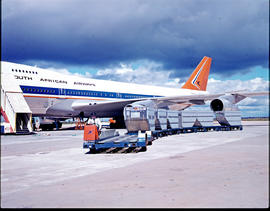 SAA Boeing 747 with baggage carts on apron.