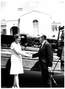 Man greeting woman with model of SAR Class 16DA locomotive on trailer. Model made by L Kennard, t...