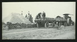 Steam tractor with trailers being loaded.
