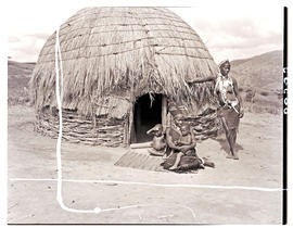 Natal, 1946. Two Zulu women with babies in front of hut.