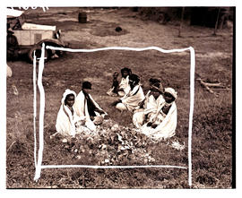 Transkei, 1940. Group of women with baby sitting on grass.