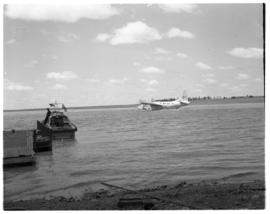 Vaal Dam, circa 1949. Arrival of BOAC flying boat Solent G-AKNS. Luggage boat with aircraft in th...