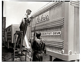 """Johannesburg, 1962. Two apprentices securing sign on container trailer at Road Transport Se..."
