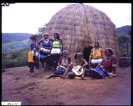 Zulus at traditional hut.