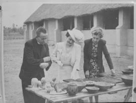 Queen Elizabeth admiring local craft accompanied by church minister and a woman.