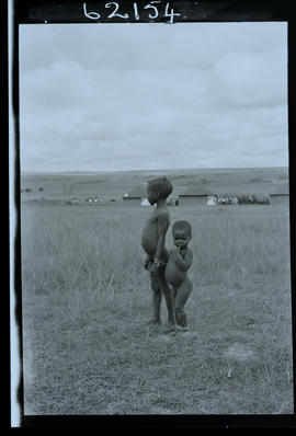 Transkei, 1954. Two young boys with kraal in the distance.