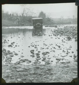 Bus fording river with stony bed.