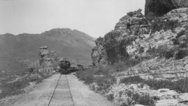Tulbagh district, 1895. Cape 6th Class locomotive with train at Bushman Rock in Tulbagh Kloof. (E...