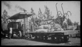 Roadrail tractor with loaded flat bed goods wagon.