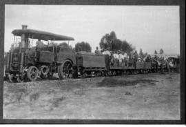 Roadrail tractor hauling train with standing passengers.