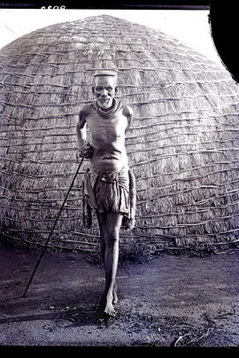 Natal. Old Zulu man leaning on stick in front of hut.