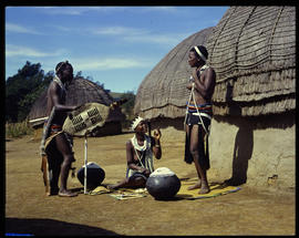 Zululand, 1961. Man and women at traditional huts.
