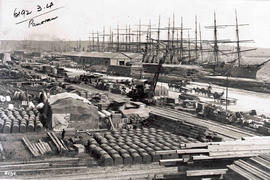 Durban, circa 1890. Sailing vessels, goods on quayside, sheds, steam crane in Durban Harbour.