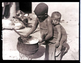 Transkei, 1932. Young boy stirring cooking pot.