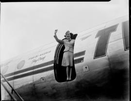 Hostess waving from open door of TWA Lockheed Constellation 'Star of Madrid'.