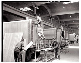 """Johannesburg, 1962. Sheetmetal workers fitting cladding on trailers in Road Transport Servi..."