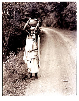 Transkei, 1940. Woman carrying pot on head.