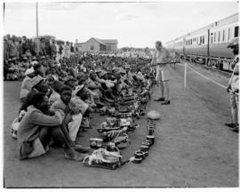 Bechuanaland, 17 April 1947. Crowd with carved and woven goods seated alongside Pilot Train at wa...