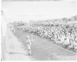 Bechuanaland, 17 April 1947. Crowd seated alongside Pilot Train at wayside station.