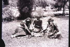 Natal. Zulu traditional healer with two women sitting on grass.