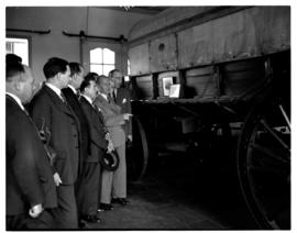 Circa 1948. Group of about 35 men on tour, admiring ox-wagon in museum.