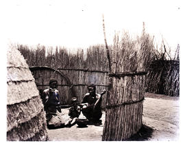 Natal. Two Zulu women and baby in reed enclosure.