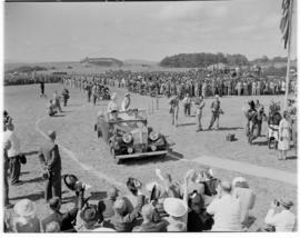 Eshowe, 19 March 1947. Queen Elizabeth and King George VI standing up in open Daimler to greet th...