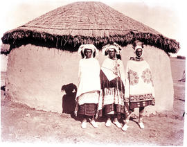 """Transkei, 1940. Three people at hut."""