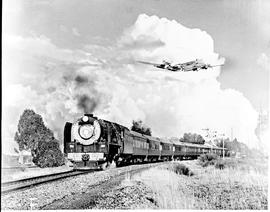 """1956. SAR Class 15F with Blue Train and aircraft overhead."""