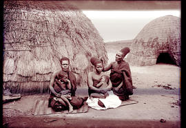 """Eshowe district, 1929. Zulu women with babies in front of hut."""