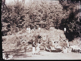 """1936. Group with motor car parked at the edge of forest."""