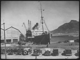 Cape Town. Row of old cars with ship in Table Bay harbour.