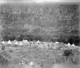 Page 24. construction camp in distance with tents and wagons. Four well dressed men relaxing in f...