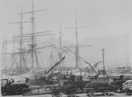 Cape Town. Table Bay Harbour scene with wagonloads in foreground and large sailing vessels in the...