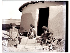 Transkei, 1952. Three Xhosa women with baby at hut.