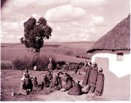 """Umtata district, 1957.Group of people at hut."""
